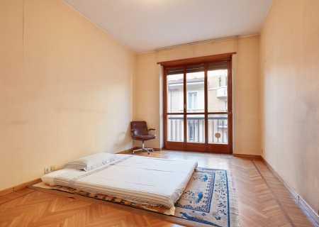 легло с матрак в средата на празна стая